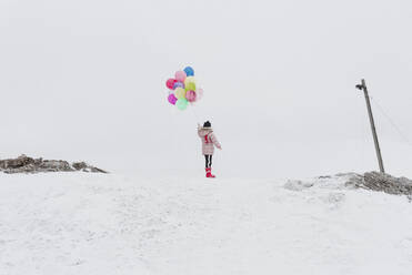Back view of girl with ballons standing on snow-covered hill in winter - PSIF00370