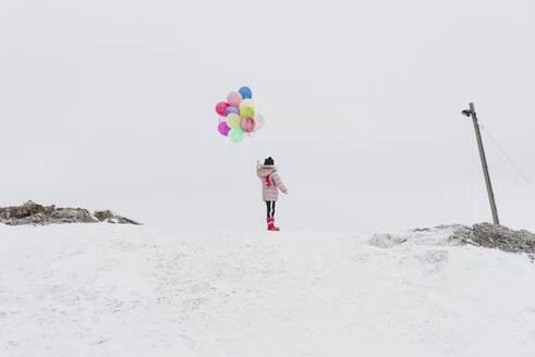 Finland, Kuopio, Kind feiert Geburtstag mit Luftballons im Schnee - PSIF00370