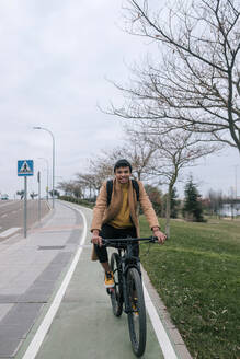 Portrait of smiling young man riding bicycle in the city - GRCF00086