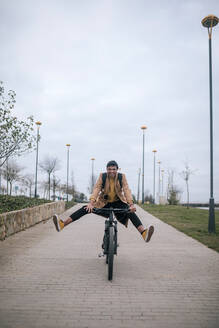 Playful young man riding bicycle in the city - GRCF00089