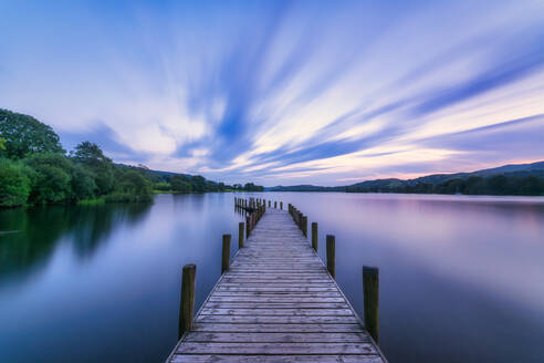 UK, England, Long exposure of clouds over jetty on Coniston Water lake at dusk - SMAF01714