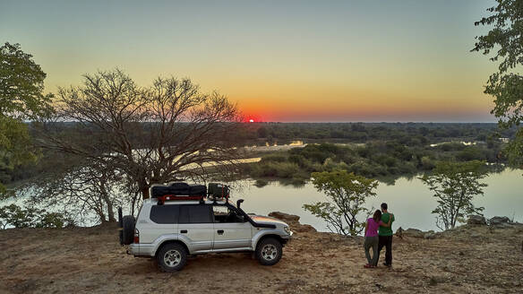 Aerial view of a couple with their jeep enjoying the sunset in front of the river, Cunene river area, Angola - VEGF01437
