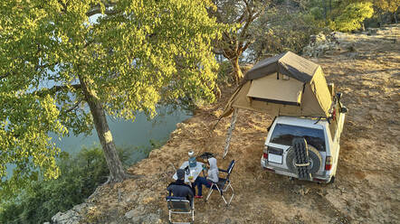 Aerial view of a couple camped with their jeep and rooftop tent and having breakfast at riverside, Cunene river area, Angola - VEGF01440
