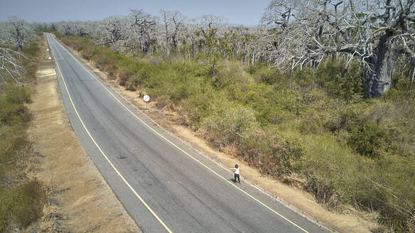 Aerial view of a woman at a road hitchhiking, Cabo Ledo area, Angola - VEGF01446