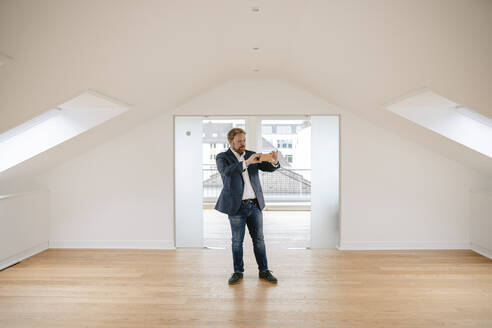 Estate agent standing in empty apartement taking pictures - GUSF03181