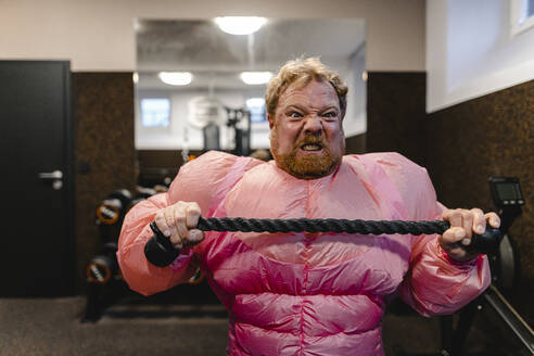 Man wearing pink bodybuilder costume practicing in gym - GUSF03223