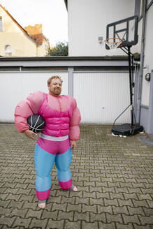 Portrait of a man with basketball wearing pink bodybuilder costume - GUSF03229