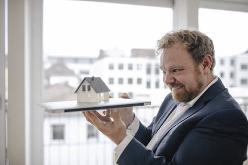 Smiling businessman holding model house in office - GUSF03250