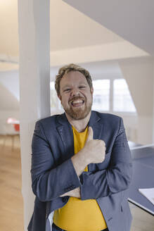 Portrait of a happy businessman in office with table tennis table - GUSF03265