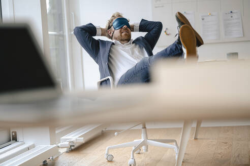 Businessman having a power nap at desk in office - GUSF03298
