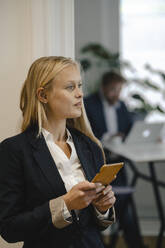 Young businesswoman with cell phone in office - GUSF03322