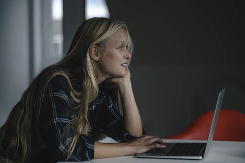 Casual young businesswoman using laptop in office - GUSF03334