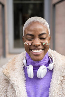 Portrait of mature white haired woman with white headphones and stickers in her face, good vibes - AFVF05012