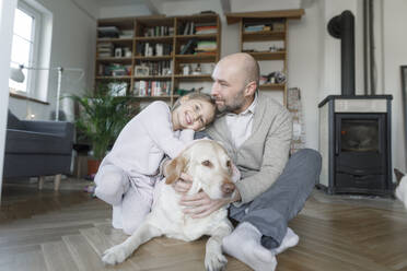 Portrait of father sitting with his little daughter and the dog on the floor at home - KMKF01202