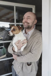 Portrait of relaxed man with dog on his arms standing at open terrace door of his house - KMKF01208
