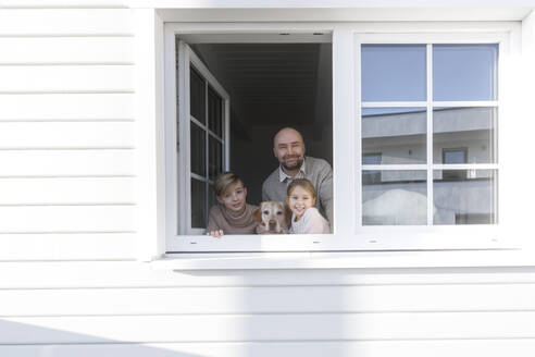 Portrait of happy father and his two children looking out of window - KMKF01211