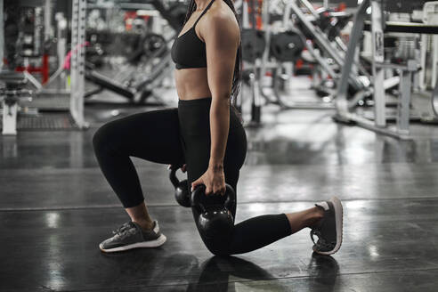 Female athlete doing lunges with kettlebells - VEGF01471