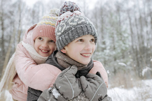 Portait of boy giving his little sister a piggyback ride in winter forest - EYAF00845
