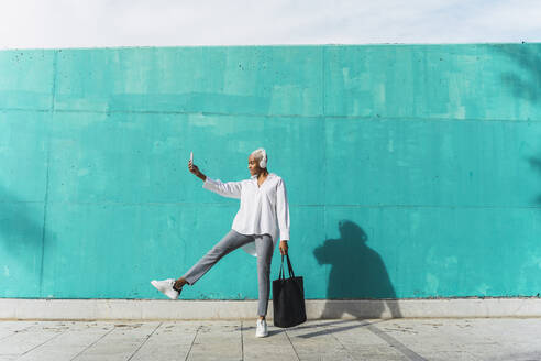 Businesswoman with headphones, standing in front of teal wall, using smartphone - AFVF05092