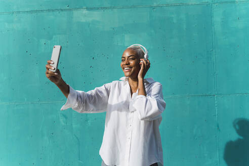 Beautiful woman standing in front of teal wall, listening music, taking selfies - AFVF05095