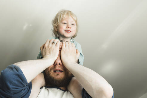 Father carrying little daughter on his shoulders at home - IHF00258