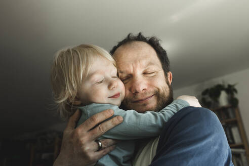 Affectionate father carrying little daughter at home - IHF00261