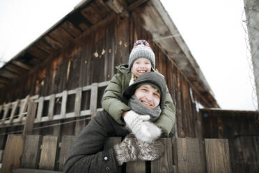 Portrait of happy father carrying daughter piggyback outdoors in winter - EYAF00865