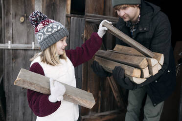 Daughter giving firewood to her father in winter - EYAF00874