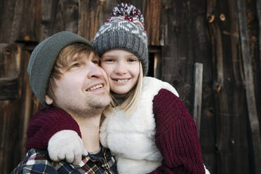 Happy daughter hugging father outdoors in winter - EYAF00880