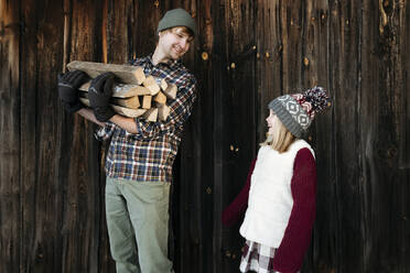 Happy father and daughter holding firewood in winter - EYAF00886