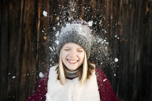Snow falling on happy girl wearing woolly hat - EYAF00892