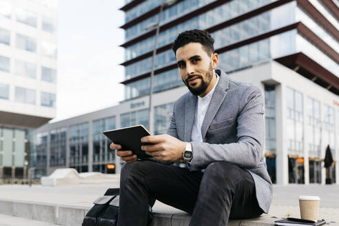 Porrait of a casual young businessman sitting on stairs in the city using tablet - JRFF03974