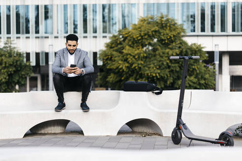 Casual young businessman sitting on a bench in the city using cell phone - JRFF03992