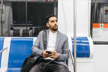 Young businessman with cell phone and earphones on the subway - JRFF04007