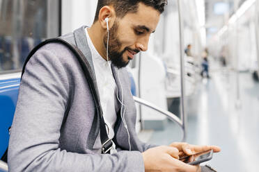 Young businessman with cell phone and earphones on the subway - JRFF04010