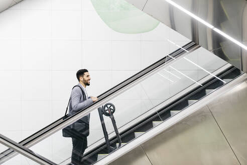 Smiling young businessman with electric scooter on escalator - JRFF04019