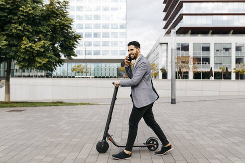 Casual young businessman with electric scooter talking on the phone in the city - JRFF04025