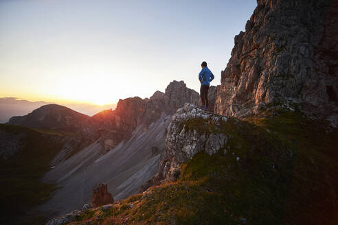 Mountain runner taking a break, watching sunrise at Axamer Lizum, Austria - CVF01526