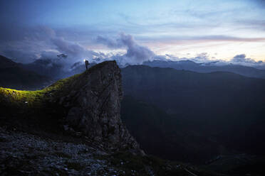 Hiker standing on rock spur at twilight, looking at the mountains - CVF01535