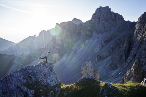 Woman balancing on rock spur, Axamer Lizum, Austria - CVF01538