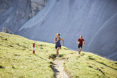 Man and woman running uphill in the mountains - CVF01550