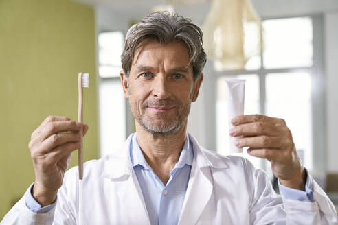 Portrait of dentist holding toothbrush and toothpaste in his medical practice - PHDF00034