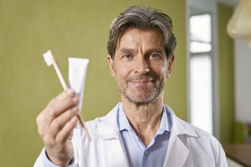 Portrait of dentist holding toothbrush and toothpaste in his medical practice - PHDF00040
