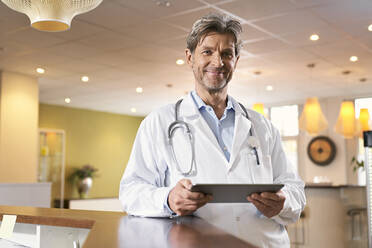 Portrait of confident doctor with tablet at reception in his medical practice - PHDF00046