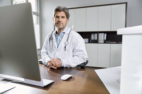 Portrait of confident doctor at desk in his medical practice - PHDF00049