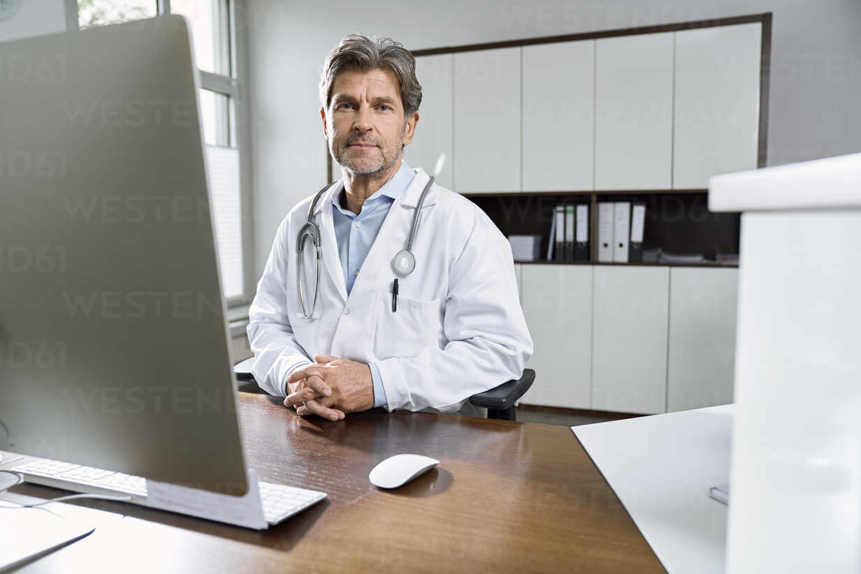 Portrait of confident doctor at desk in his medical practice - PHDF00049 - Isabella Bellnini/Westend61