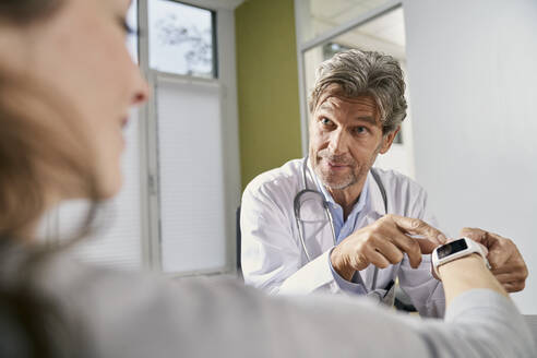 Doctor checking smartwatch of female patient in his medical practice - PHDF00061