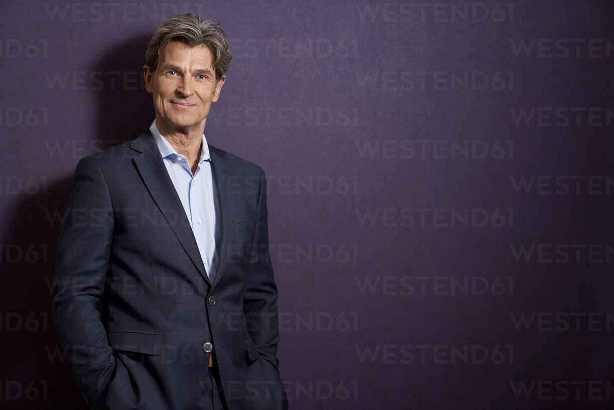 Portrait of confident businessman in front of a purple wall - PHDF00070 - Isabella Bellnini/Westend61