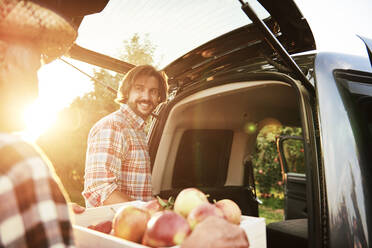 Fruit grower loading car with apple crates - ABIF01279
