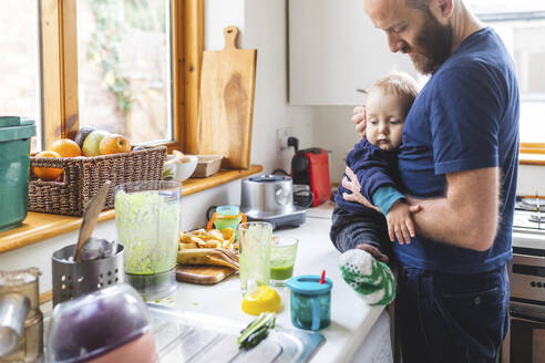 Man in the kitchen preparing food and cuddling his son - WPEF02460